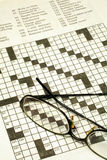 Crossword Puzzle and Glasses. This is a close up image of a crossword puzzle an a pair of glasses royalty free stock photo