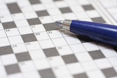 Crossword puzzle with pen. Close-up of a ball point pen resting on a blank crossword Stock Images