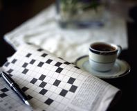 Crossword puzzle with pen and black coffe. E Stock Photos