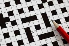 Crossword puzzle. Solving a crossword puzzle with red pencil