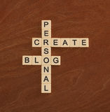 Crossword puzzle with words Create Personal Blog. Social networking concept. Ivory tiles with capital letters on mahogany board Stock Images