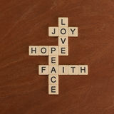 Crossword puzzle with words Faith, Hope, Love. Faith concept. Ivory tiles with capital letters on mahogany board stock photos