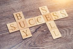 Crossword of success mindset letters. Buy and sell words on a wooden desk. Crossword of success mindset letters. Buy and sell words motivation concept stock photo
