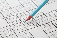 Crossword sudoku and blue pencil for entertainment Royalty Free Stock Photos