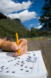Crosswords. Doing crosswords in a sunny mountein day.Really blue sky with white clouds Royalty Free Stock Photo