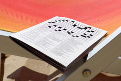 Crosswords on the sand deckchair Stock Images