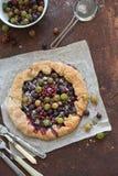 Crostata或galette饼用在难看的东西生锈的金属背景,顶视图的新鲜的庭院莓果 库存图片