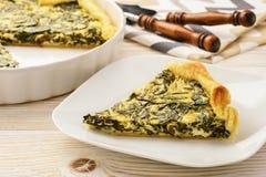 Crostata con spinaci e le uova su fondo bianco Immagine Stock