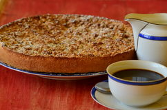 Crostata della briciola della prugna con la tazza di caffè e la scrematrice su fondo rosso Immagine Stock
