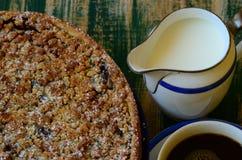Crostata della briciola della prugna con la tazza di caffè e la scrematrice su fondo verde Fotografia Stock