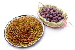 Crostata della prugna prima di cuocere e un canestro con le prugne fresche Fotografia Stock