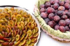 Crostata della prugna prima di cuocere e un canestro con le prugne fresche Fotografia Stock Libera da Diritti