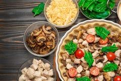 Crostata tradizionale della quiche nella forma bollente con materiale da otturazione e gli ingredienti fotografia stock