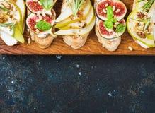 Crostini用梨、乳清干酪乳酪,无花果,胡说和新鲜的草本 库存照片