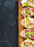 Crostini用梨、乳清干酪乳酪,无花果,胡说和新鲜的草本 免版税库存图片