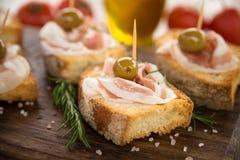 Crostini用烟肉和橄榄,意大利手抓食物 免版税库存照片