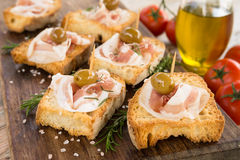 Crostini用烟肉和橄榄,意大利手抓食物 免版税库存图片