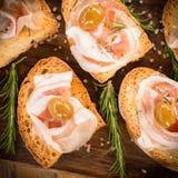 Crostini用烟肉和橄榄,意大利手抓食物 免版税图库摄影