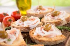 Crostini用烟肉和橄榄,意大利手抓食物 库存照片