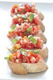 Crostini用蕃茄、蓬蒿和大蒜 库存图片