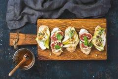 Crostini с плодоовощами, сыром и травами на деревенской деревянной доске Стоковые Фотографии RF