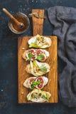 Crostini с плодоовощами, сыром и травами на деревенской деревянной доске Стоковая Фотография RF