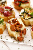 Crostini with addition of chanterelle mushrooms and melted cheese on white table closeup Stock Images