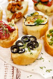 Crostini with addition of melted mozzarella cheese,  black olives and fresh thyme Stock Photo
