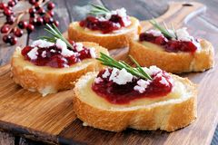 Crostini appetizers with cranberry sauce, cheese, rosemary on wooden server Royalty Free Stock Photography