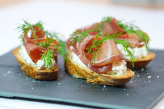 Crostini with bacon. Goat cheese and dill topping Royalty Free Stock Photo
