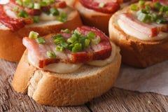 Crostini with bacon and mozzarella macro on the table. horizonta Stock Photography