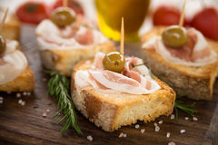 Crostini with bacon and olives, Italian Finger Food Royalty Free Stock Photos