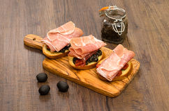Crostini with black tapenade and raw ham. On a wooden board Royalty Free Stock Photography