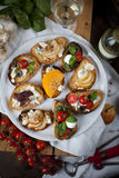 Crostini and bruschetta with cheese, pears, persimmon and honey. Plate of crostini and bruschetta with gorgonzola, mozzarella, vine tomatoes, basil, persimmon Royalty Free Stock Photography