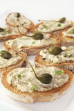Crostini with Capers. Crostini or bruschetta, topped with a mix of pecorino cheese, tuna and capers, garnished with a caperberry Stock Images