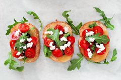 Crostini with cherry tomatoes, arugula, and cheese, above on marble Stock Photos