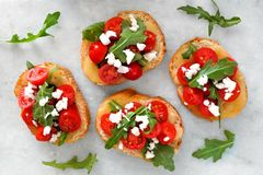 Crostini with cherry tomatoes, arugula, and cheese on marble Stock Photo