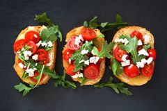 Crostini with cherry tomatoes, arugula, and cheese on slate Stock Image
