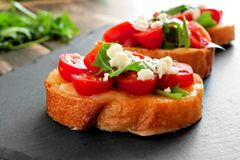 Crostini with cherry tomatoes, arugula, and cheese on slate server Stock Photography