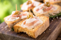 Crostini con el tocino y las aceitunas, comida para comer con los dedos italiano Foto de archivo