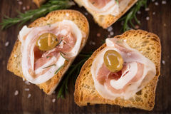 Crostini con el tocino y las aceitunas, comida para comer con los dedos italiano Imagen de archivo
