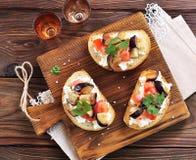 Crostini con formaggio a pasta molle, melanzana, i pomodori e l'aglio Fotografia Stock Libera da Diritti