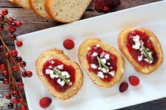 Crostini con la salsa de arándano, el queso y el romero, escena de arriba Imagenes de archivo
