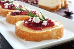 Crostini con los arándanos, queso, romero cercano para arriba en la placa blanca Fotos de archivo libres de regalías