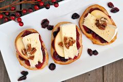Crostini with cranberry sauce, apples, brie and pecans, above view Stock Photos