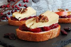 Crostini with cranberry sauce, apples, brie and pecans on slate Royalty Free Stock Images