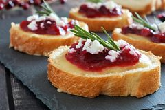 Crostini with cranberry sauce, cheese, rosemary close up on slate Royalty Free Stock Photography