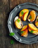 Crostini with cream cheese and fresh peaches on vintage plate. Royalty Free Stock Images