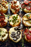 Crostini with different toppings on dark background.  Delicious appetizers Stock Photo
