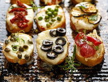 Crostini with different toppings on dark background.  Delicious appetizers Stock Photos